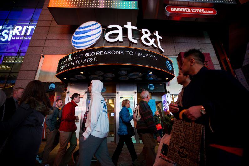 Pedestrians walk past an AT&T Inc. store in the Times Square area of New York, U.S., on Saturday, Oct. 22, 2016. According to a statement Saturday, AT&T agreed to buy Time Warner for $107.50 a share. Photographer: Michael Nagle/Bloomberg